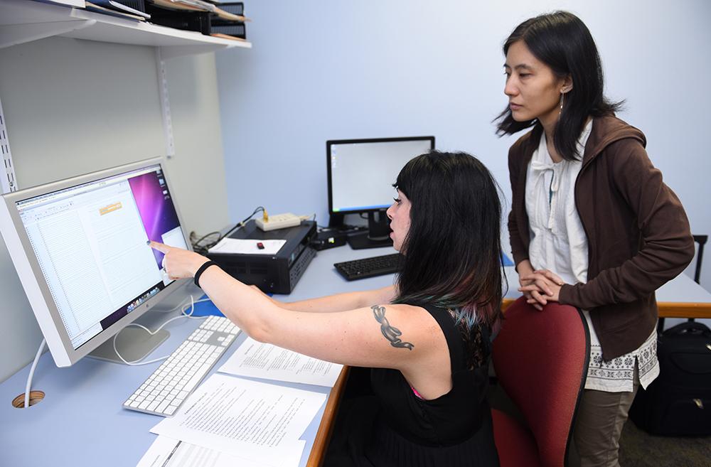 photo of speech pathology students anaylzing their work on a computer