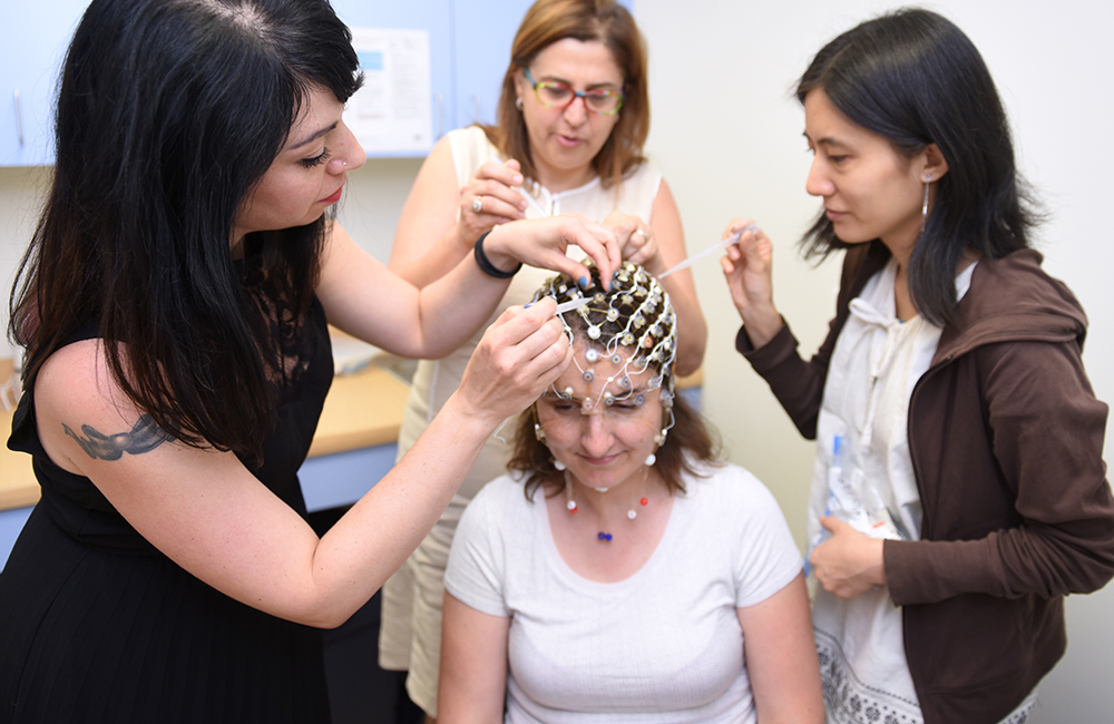 Adelphi students working with a sensor net for EEG