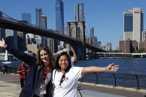 Two Adelphi students in Manhattan with the Brooklyn Bridge in the background.