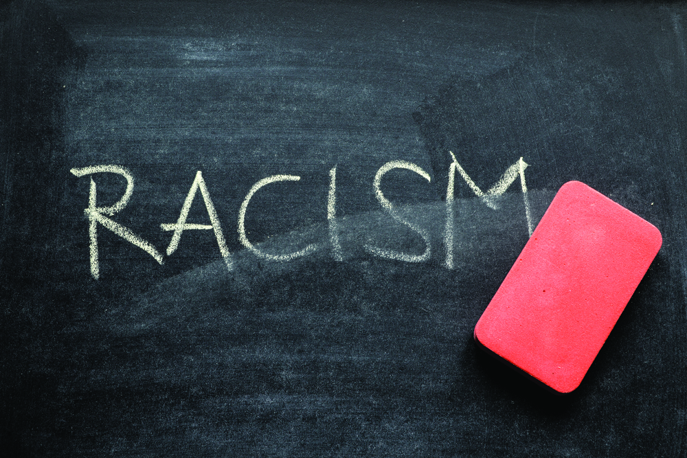 The word racism on a chalkboard being erased