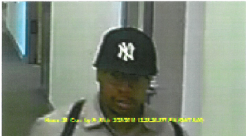 Alleged perpetrator of the grand larceny: male, African American, wearing round eyeglasses, a Yankee baseball hat, and a light colored jacket carrying a backpack and may be carrying loose papers in his hand.