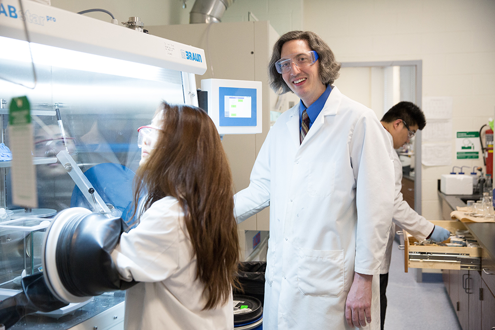 A professor in the lab with students